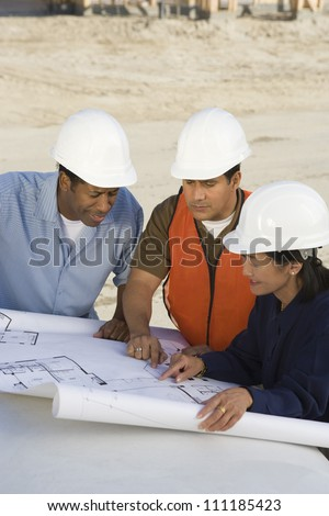 Three architects at construction site - stock photo