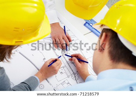 Three architects correcting a construction plan - stock photo