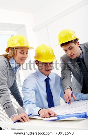 Three architects sitting at table and discussing a housing plan - stock photo