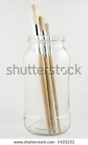 Three artists' paint brushes standing in a jar - stock photo