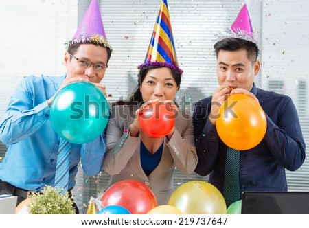 Three Asian business colleagues blowing up balloons and looking at the camera - stock photo