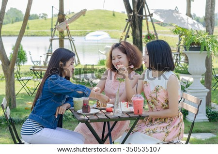Three Asian girl eating cake and drink together at cafe - stock photo