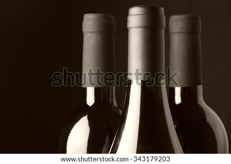 Three assorted wine bottles close-up on black background. Monochrome sepia toned image. Focus on front bottle. - stock photo