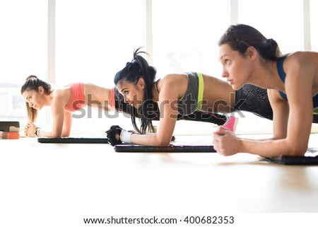 Three attractive sport girls doing plank exercise lying on yoga mat in fitness class.  - stock photo