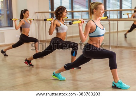 Three attractive sport girls smiling, holding barbell and squatting while working out in fitness class - stock photo
