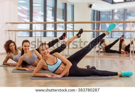Three attractive sport girls smiling while working out lying on their side on yoga mat in fitness class - stock photo