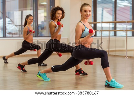 Three attractive sport girls smiling while working out with dumbbells and doing lunges in fitness class - stock photo