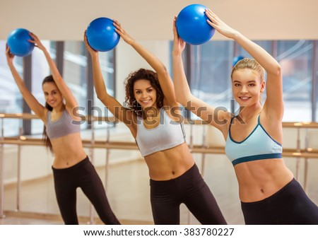 Three attractive sport girls smiling while working out with fitness ball in fitness class - stock photo