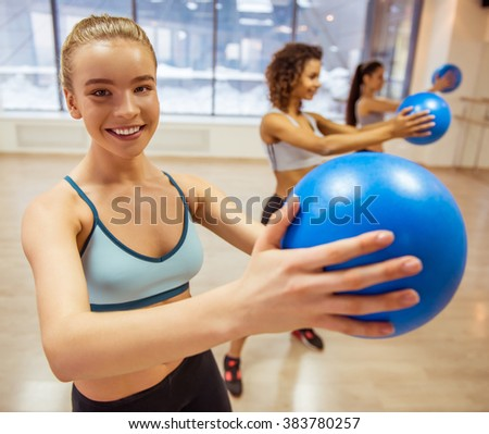 Three attractive sport girls smiling while working out with fitness ball in fitness class. Beautiful blonde girl looking at camera - stock photo