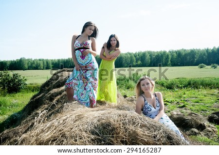Three attractive women standing on hay stack - stock photo