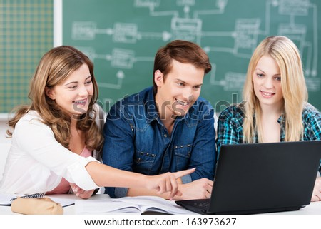 Three attractive young college students studying together in class sitting at a desk sharing a laptop computer and smiling as they point at the screen - stock photo