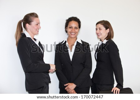 Three attracttive elegant multiethnic young businesswomen in black business suits standing together having a discussion and smiling at the camera - stock photo