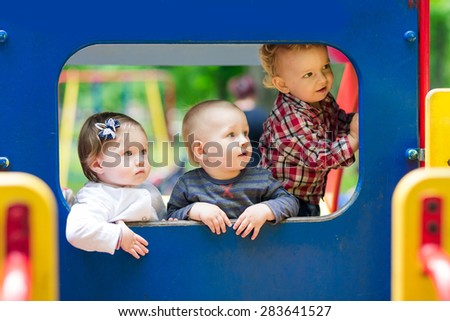 Three babies in the toy car on the playground - stock photo