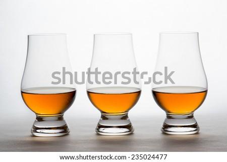 Three backlit crystal glasses containing amber liquor.  Whiskey, bourbon, brandy, etc. - stock photo
