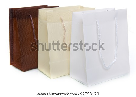 three bags, a brown, a white and a creme one, on a white background - stock photo