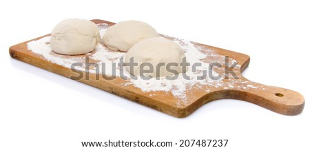 Three balls of pizza dough on a wooden board, isolated on white - stock photo