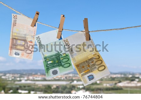 three banknotes are hanging on a string - stock photo
