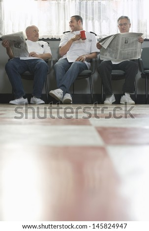 Three barbers waiting for customers in barbershop - stock photo