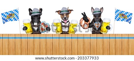 three bavarian  dogs behind a fence with beer mugs and pretzel bread - stock photo