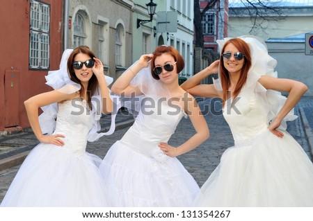 Three beautiful brides in sunglasses - stock photo