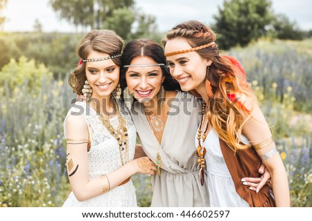 Three beautiful cheerful hippie girls, best friends, laughing, posing for the camera, trendy hairstyles, feathers in her hair, white dress, tattoo flash, accessories, Bohemian, Bo-ho Style, indie - stock photo