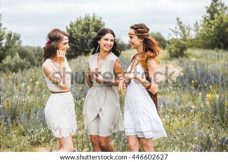 Three beautiful cheerful hippie girls, best friends, outdoors, laughing, having fun, stylish hairstyle, feathers in her hair, white dress, tattoo flash, gold accessories, Bohemian, bo-ho style fashion - stock photo