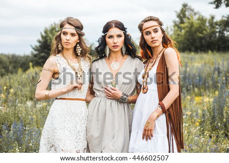 Three beautiful cheerful hippie girls, best friends, the outdoors, trendy hairstyles, feathers in her hair, white dress, tattoo flash, gold accessories, Bohemian, bo-ho style, fashion,  indie - stock photo