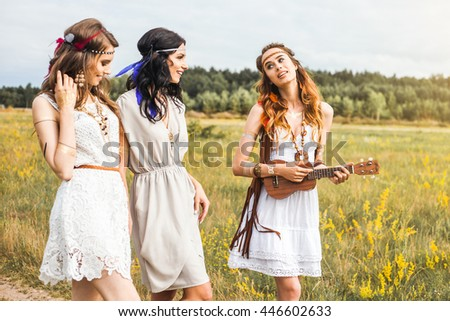Three beautiful cheerful hippie girls, outdoors, trendy hairstyles, feathers in her hair, white dress, tattoo flash, gold accessories, Bohemian, bo-ho style, Funny time for the best friends. Lifestyle - stock photo
