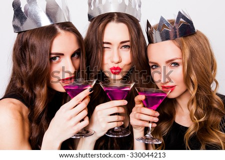 Three beautiful elegant women celebrate hen-party and drinking cocktails. Best friends wearing black stylish evening dress, high heel shoes ,crown on head .Bright make up, red lips. Inside. - stock photo