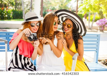 Three beautiful fashion girl happy hipster, travel, best friends, sitting on a bench in the airport waiting area, with suitcases and the camera in sunglasses, hats, bright fashionable clothes laughing - stock photo