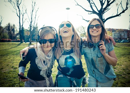 three beautiful friends authentic in urban contest listening to music - stock photo