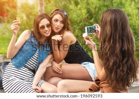 Three beautiful girlfriends make: sending kiss photo - stock photo