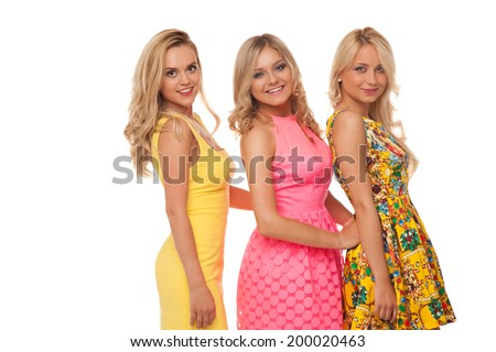 three beautiful girls in fashion dresses isolated on white  - stock photo