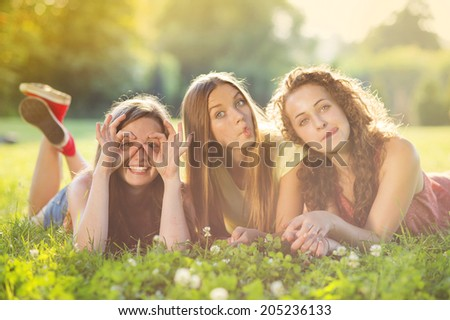 Three beautiful girls laughing together and lying on grass outdoors in a park. - stock photo