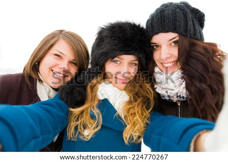 Three beautiful girls taking a selfie outdoors in the snow. - stock photo