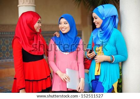 Three beautiful muslim girls having fun talking each other - stock photo