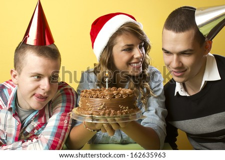 Three beautiful people on the New Year's Eve with cake - stock photo