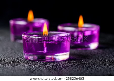 three beautiful purple candles on a black background with water drops - stock photo