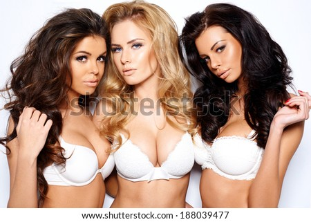 Three beautiful sexy curvaceous young women modeling white bras showing off their ample cleavages as they pose arm in arm looking seductively at the camera - stock photo