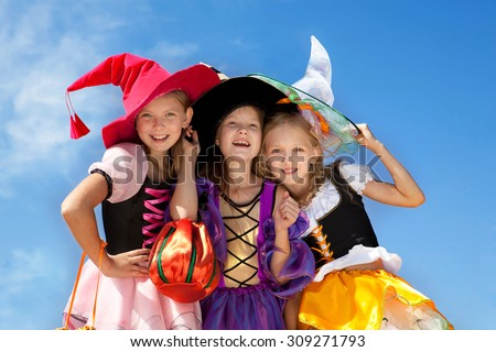 Three Beautiful Smiling Little Girls with Long Hair in the Witch Costume Looking at Camera with Trick or Treat Bags at the Blue Sky.