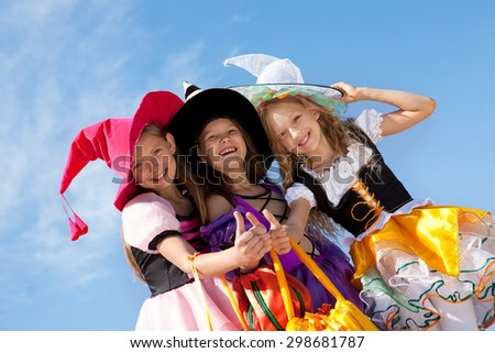 Three Beautiful Smiling Little Girls with Thumbs Up in the Colorful Witch Costumes Looking at Camera with Trick or Treat Bags. - stock photo