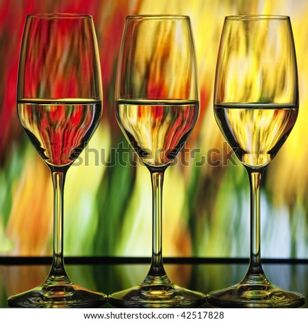 Three beautiful wine glasses with orange, green and yellow lighted background which looks like fire - stock photo