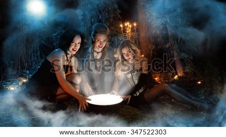 Three beautiful witches are making magic. Dark forest on the background. - stock photo