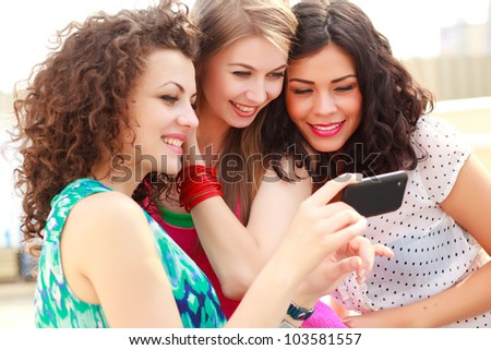 three beautiful women smiling while looking on a smart-phone - stock photo