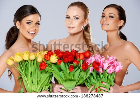 Three beautiful women with bunches of fresh spring tulips held to their chests smiling at the camera, head and shoulders portrait - stock photo