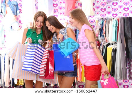 Three beautiful young woman in shop with shopping bags - stock photo