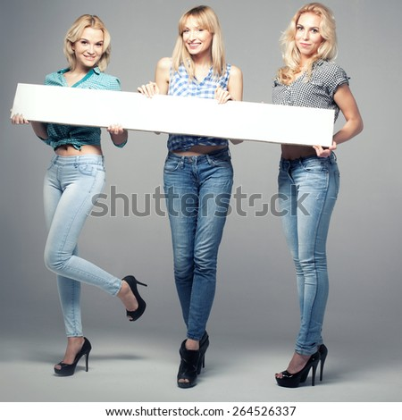 Three beautiful young woman posing in fashionable jeans, holding empty board. Blonde girls. Studio photo. - stock photo