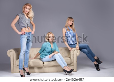 Three beautiful young woman posing in fashionable jeans, looking at camera. Blonde girls. Studio photo. - stock photo
