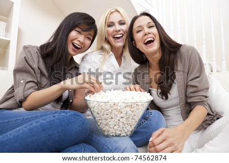 Three beautiful young women friends at home eating popcorn watching a movie together and laughing - stock photo