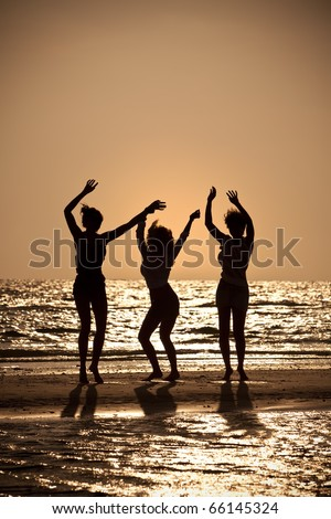 Three beautiful young women in bikinis dancing on a beach at sunset all in silhouette - stock photo